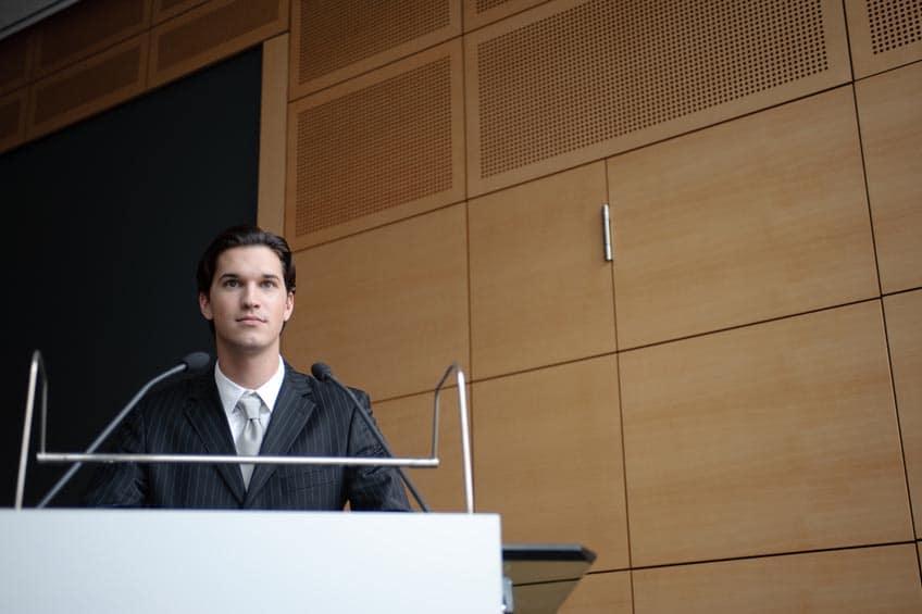 Homme derrière un pupitre qui s'apprête à faire un discours