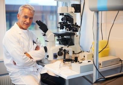 scientifique assis devant un microscope