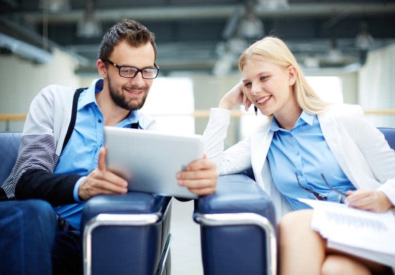 2 personnes qui regardent l'écran d'une tablette