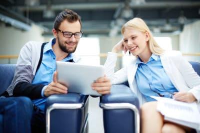Une femme et un homme qui regardent quelque chose sur l'écran d'une tablette tactile.