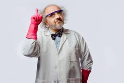 Scientifique avec une noeud papillon, des gants roses, des lunettes bleues et qui lève le doigt avec un regard comique