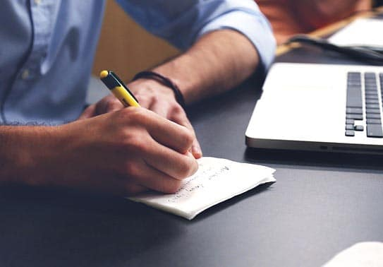 Homme devant un ordinateur qui écrit sur une feuille de papier ses idées pour une rédaction scientifique