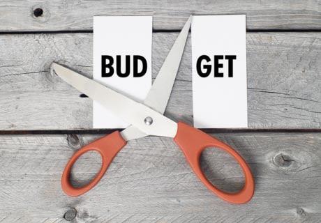 """Le mot budget écrit sur une feuille coupée en deux entre """"BUD"""" et """"GET"""" par des ciseaux"""