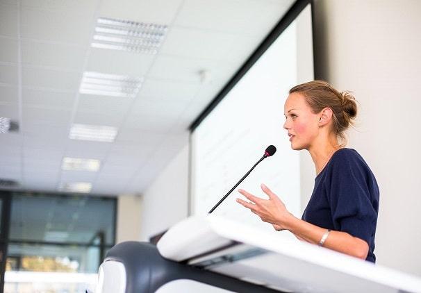 Femme derrière un pupitre avec un micro qui s'exprime devant une assemblée