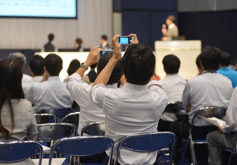 Conférence où 2 personnes du public prennent en photo les intervenants et la présentation PowerPoint