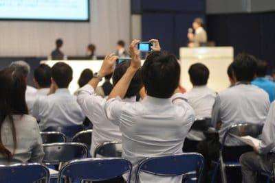 2 participants à une conférence qui prennent en photo l'intervenant.