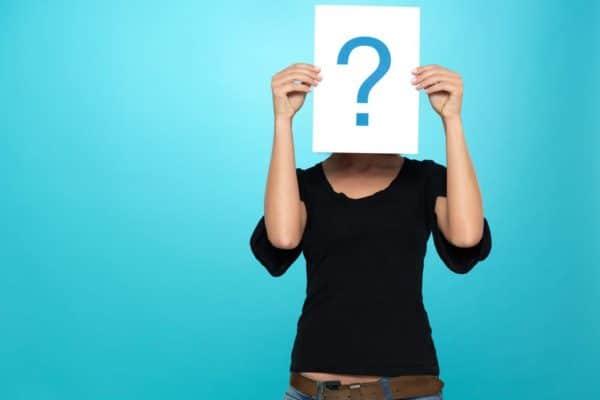 Femme tenant une feuille blanche avec un point d'interrogation dessiné dessus.