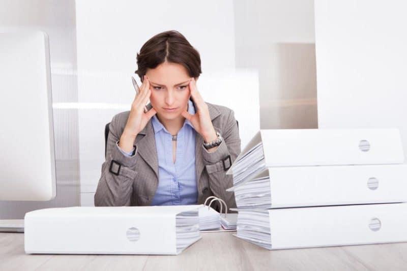 Photo d'une femme stressée au travail devant une pile de classeurs