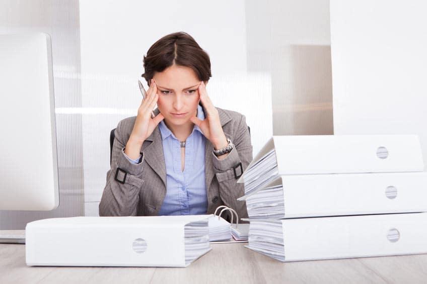 Femme à son bureau, avec une pile de classeurs devant elle, qui se tient la tête entre les mains, l'air dépassé par la situation