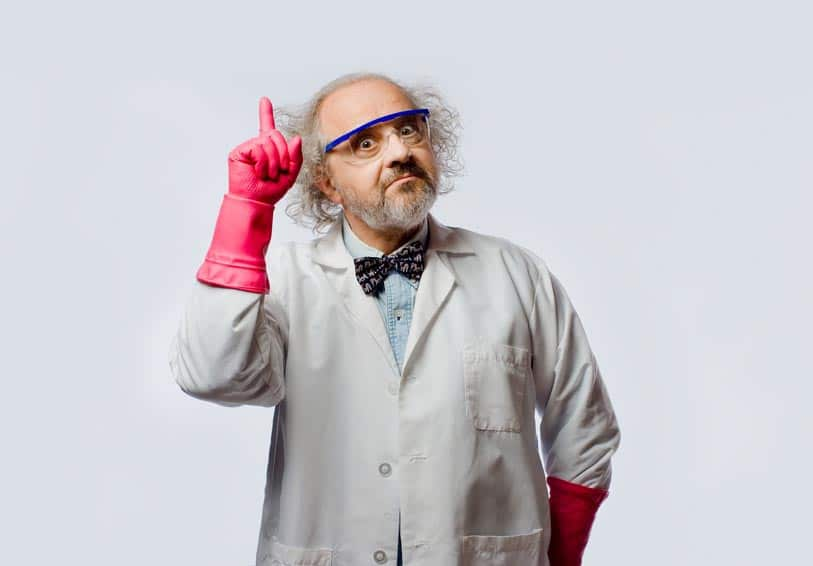 Scientifique avec un noeud papillon, des gants roses et des lunettes bleues, qui lève le doigt avec un regard comique