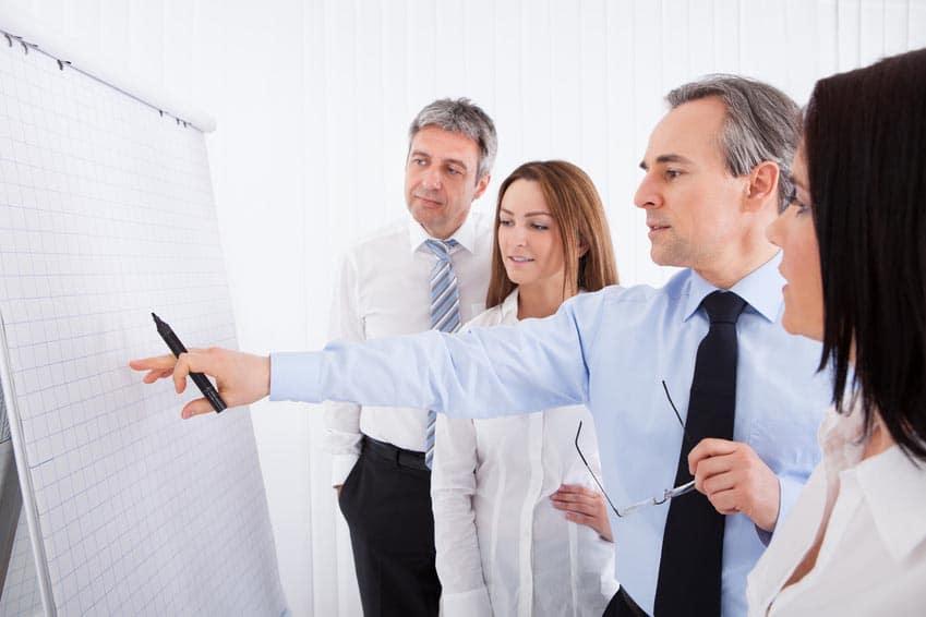 4 personnes qui discutent devant un paperboard sur lequel ils s'apprêtent à écrire