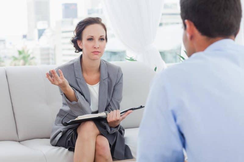 Femme d'affaires en réunion avec un homme. Elle lui pose une question.