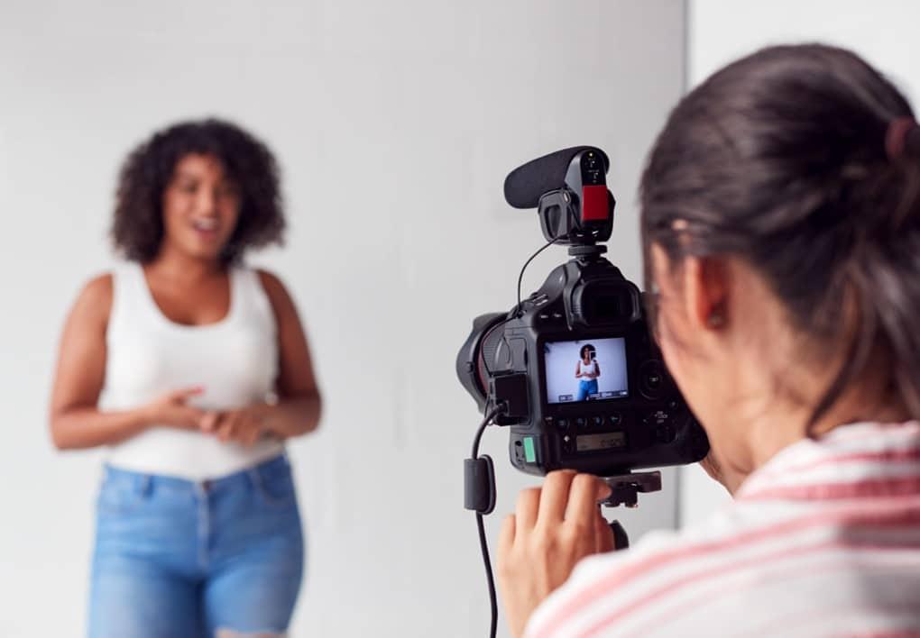vidéaste qui filme une femme en train de parler devant la caméra