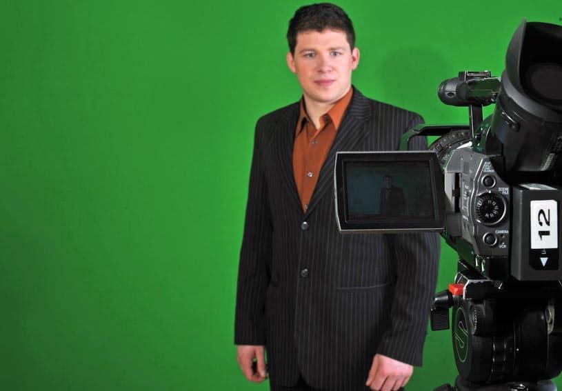 Homme filmé par une caméra devant un fond vert pour une vidéo