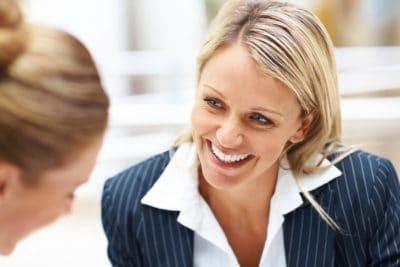 Femme d'affaire souriante qui discute avec une cliente